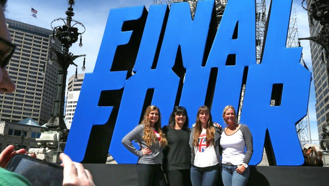 Michigan State fans Deanna Olsen, Clarkston, Mich. (second from left), has her photo taken in front of the Final Four logo on Monument Circle with daughters (from left) Paige Olsen, Dana Olsen and Rebecca Olsen as they enjoy the fun in downtown Indianapolis during the NCAA Men's Final Four weekend on Sunday, April 4, 2015. Paige and Dana attend the University of Indianapolis. Thousands of fans also attended the Final Four Fan Fest in the Indiana Convention Center.