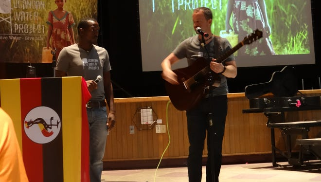 Collins Alinaitwe and James Harrington of the Ugandan Water Project team share their music and message with students in the Dryden High School auditorium.