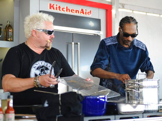 "This Feb. 26, 2017 photo made available by WorldRedEye.com, shows rapper Snoop Dog, right, and Chef Guy Fieri, cooking together during a demonstration at the South Beach Wine & Food Festival in Miami Beach, Fla. Rappers Snoop, Action Bronson and Rev Run are ushering the culinary world into an era where shows like """"Martha and Snoop's Potluck Dinner Party"" are a hit and rappers like 2 Chainz drop cookbooks along with their albums."