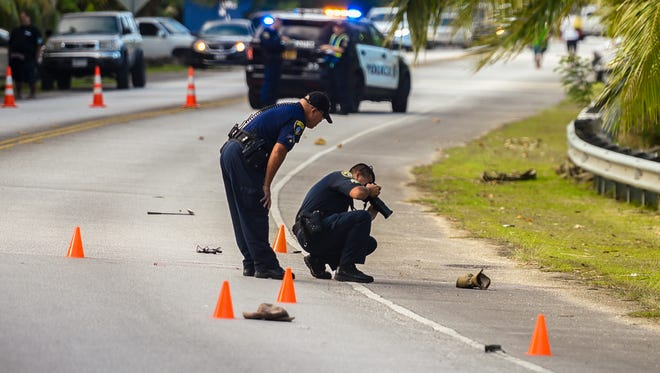 Guam Police Department forensics officer Carl Castro photographs the scene of an auto-pedestrian incident on Route 2, just north of the Agat Marina, on Sunday, April 1, 2018. At about 5:40 a.m., a passerby traveling along the roadway, discovered a male individual laying on the roadway, who appeared to be lifeless and unresponsive, according to Sgt. Paul Tapao, Guam Police Department spokesman. CPR was being administered to the man, as he was being transported to the Naval Hospital Guam. Officers of the GPD's Highway Patrol Division were activated to conduct an investigation of the incident.