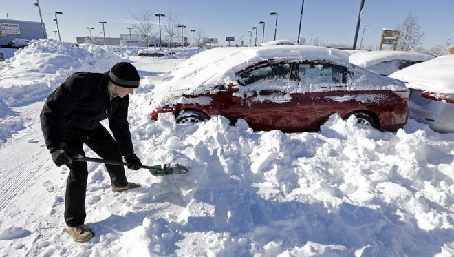 A salesman digs out cars in January at a dealership in Indianapolis, as temperatures hovered around zero.  AP FILE - In this Tuesday, Jan. 7, 2014, file photo, a salesmen at a car dealer digs out cars covered in snow at a dealership in Indianapolis, as temperatures hovered around zero.  The subzero cold followed inches of snow and high winds that made traveling treacherous. (AP Photo/Michael Conroy, File)