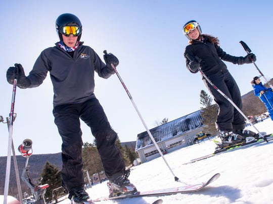 Brother and sister alpine skiers Joseph and Gigi Vasile click into their skis before hitting the slopes at Bristol Mountain on Feb. 20, 2016.