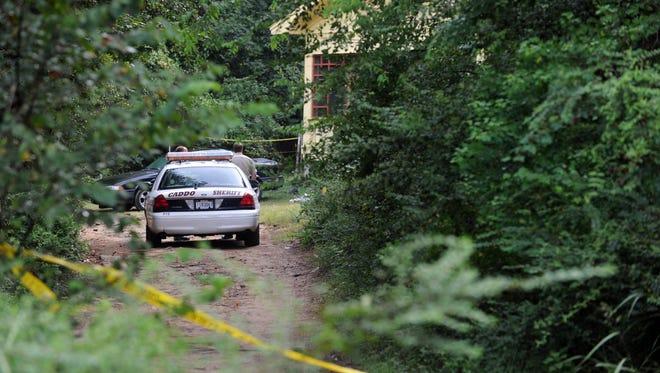 Caddo deputites on scene of a triple homicide on Keatchie-Marshall Road near state Highway 169.
