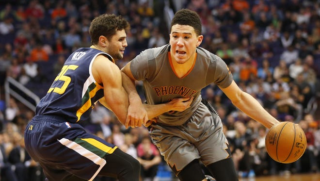 Phoenix Suns guard Devin Booker (1) is fouled by Utah Jazz guard Raul Neto (25) during the fourth quarter at Talking Stick Resort Arena in Phoenix January 16, 2017.