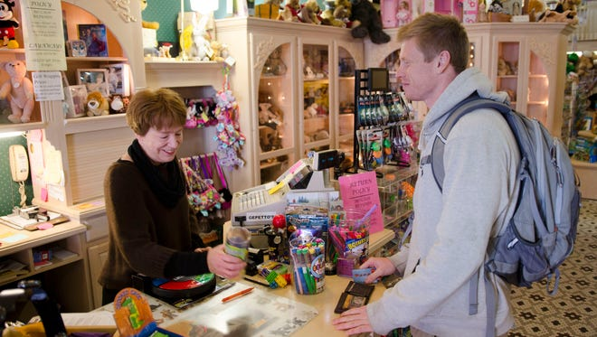 Owner Bonnie Brown-Pnazek rings up customer Troy Johnson at Gepetto's Workshop in downtown Stevens Point.