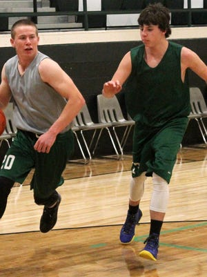 Zach Camino, left, drives past Kasen Flotte during practice Monday evening at the Cloudcroft High School gymnasium.