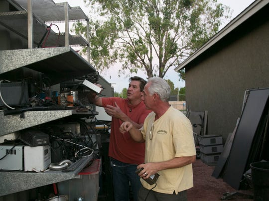 Charlie Vierhout (Right) and Lance Greathouse find parts for a broken motorized scooter to fix up at Greathouse's garage in Phoenix, AZ on Thursday, Sept. 25, 2014.