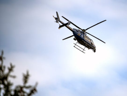 A Michigan State Police helicopter flies over the scene