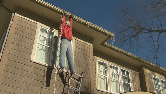 This isn't a person dangling from the roof. It's a Christmas decoration designed as a prank.