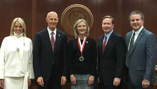 Nardi Routten (center), a teacher at C. A. Moore Elementary School in St. Lucie County, was honored with the Shine Award by Governor Rick Scott for making significant contributions to the field of education.