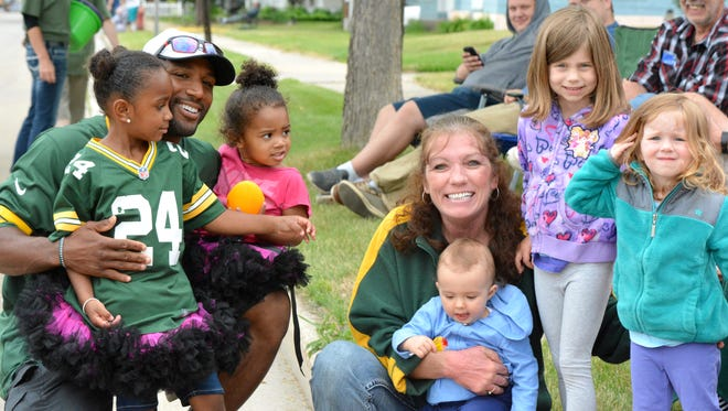 "Former Green Bay Packers cornerback Jarrett Bush stopped along the Copperfest parade route on June 9 for pictures with local fans. From left are Bush and his family, Mary Pecha and granddaughter Isabella, Mila Jenkins, and Alee Jenkins. Bush attended as a guest with Bellin Health, which entered the ""MASH"" float in the annual parade."