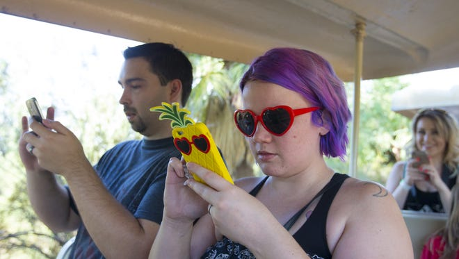 Justin Miller, 31, and Hollie Reihl, 28, of Scottsdale, play Pokemon Go on PokeShuttle at the Phoenix Zoo on Saturday, July 23, 2016.
