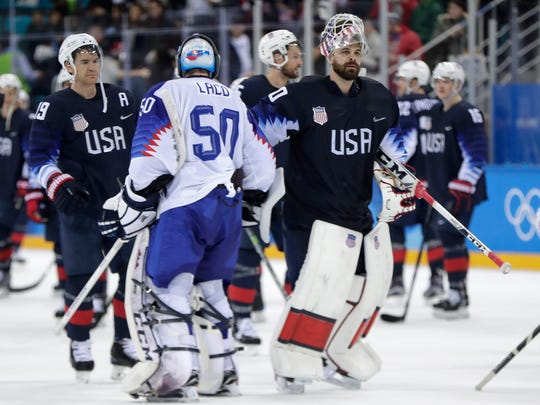 Goalies Jan Laco (50), of Slovakia, and Ryan Zapolski (30), of the United States, greet each other adfter the qualification round of the men's hockey game at the 2018 Winter Olympics in Gangneung, South Korea, Tuesday, Feb. 20, 2018. The United States won 5-1. (AP Photo/Julio Cortez)
