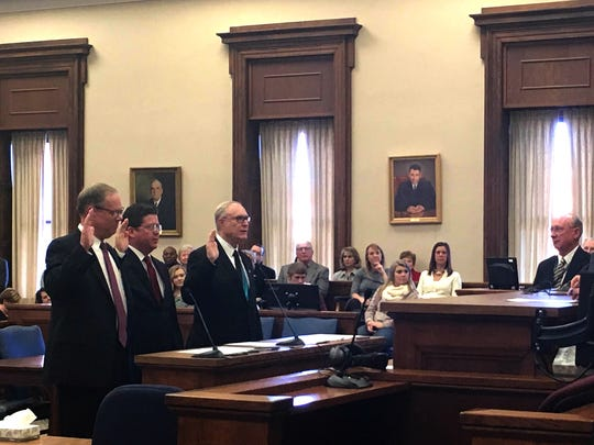 President Judge Carol van Horn, standing at right, swears in returning Franklin County Commissioners Bob Ziobrowski, David Keller and Robert Thomas.