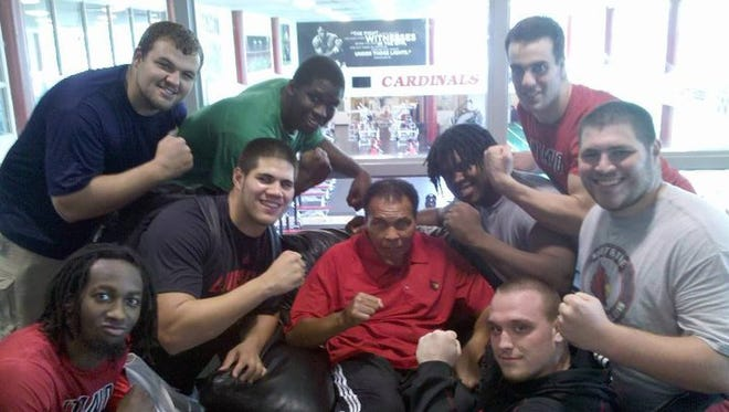 Muhammad Ali flexes with members of the 2010 University of Louisville Cardinals football team.