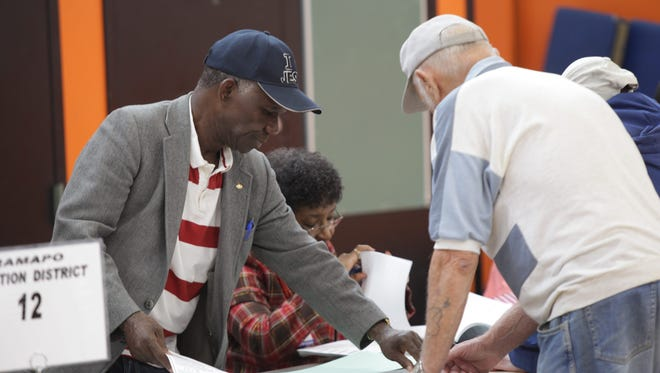 The Rev. Elijah Peters helps Ilya Geyfman sign in during the Democratic primary at Spring Valley High School on Sept. 9, 2014