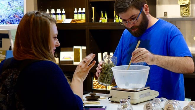 Stephanie Hess watches budtender Kyle Wells use chopsticks to weigh out marijuana for sale at Zion Cannabis in downtown Portland, Ore.