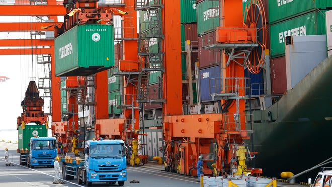 In this Oct. 21, 2015 file photo, workers watch shipping and discharging of containers at a port in Tokyo.