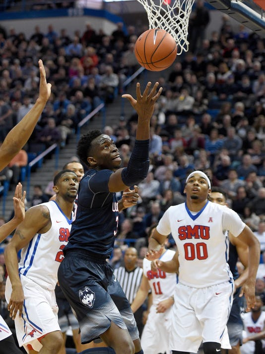 Connecticut's Amida Brimah (35) grabs a rebound as SMU's Ben Moore (00) looks on during the first half of an NCAA college basketball game in Hartford, Conn., on Thursday, Feb. 18, 2016. (AP Photo/Fred Beckham)