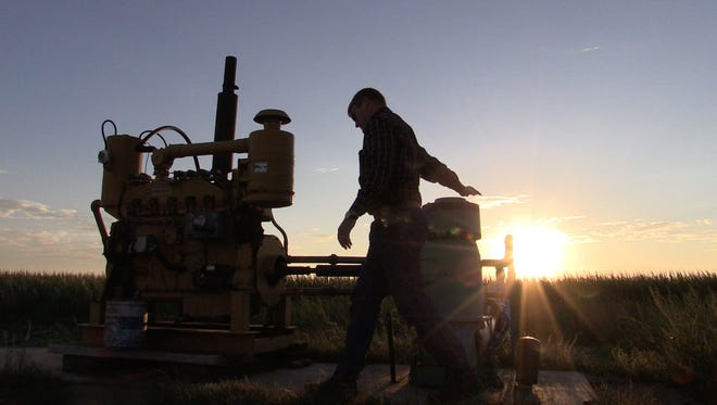 """Jay Garetson checks on a well on his family's farm near Sublette, Kansas. He came to the well at dawn after receiving an automated alert on his phone warning of """"low pressure"""" at the site. He said the well appears to be weakening and will likely be able to pump less in the coming years as the aquifer declines."""