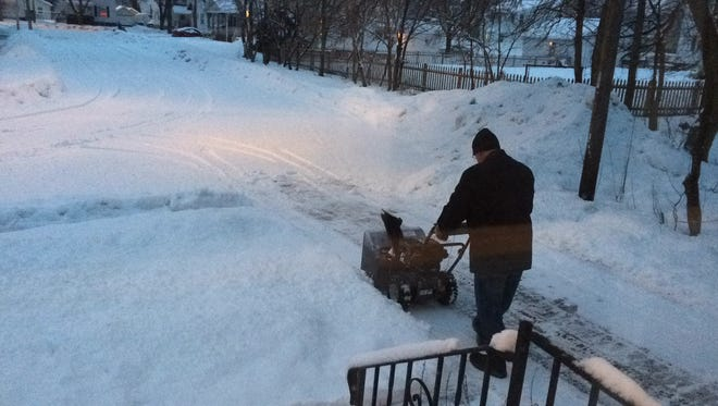 A Fort Howard resident kindly removes snow his neighbor's driveway after a recent storm.