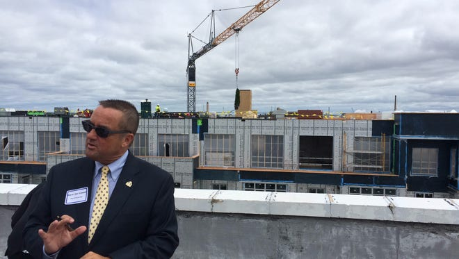 Green Bay Mayor Jim Schmitt talks about the topping off of the Metreau Apartments building on Tuesday.