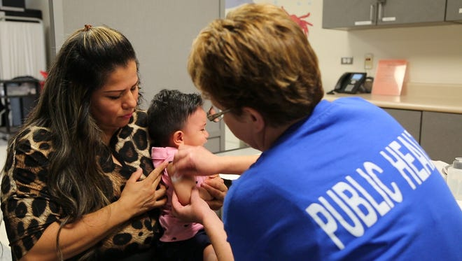 Registered nurse Diane Dickinson prepares Marcia Rodriguez's child for a vaccination. Arizona schools are required by state law to suspend students who are not vaccinated and do not have exemptions, but an official said the state lacks enforcement measures behind the law.