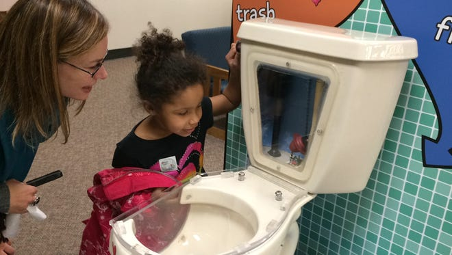 Gracie Duffus, 6, checks out the display at the Brown County Central Library, while NEW Water spokeswoman Tricia Garrison looks on.