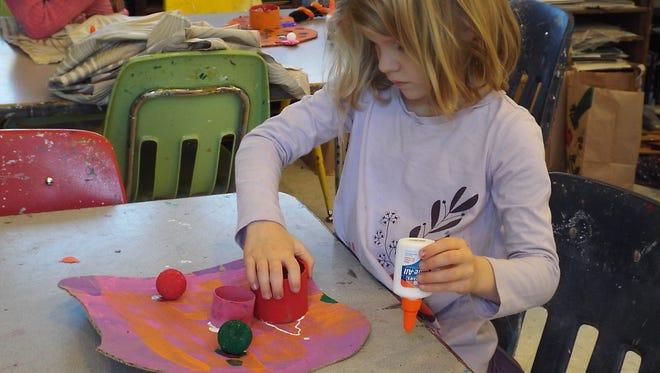 Dutchess Day Kindergartener Anna Colman works on a monster mask.
