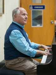Composer Allen Pote plays the piano during choir rehearsal