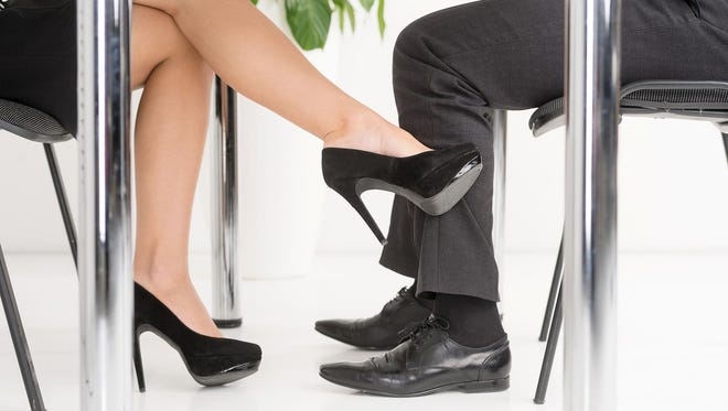 A woman's foot looking for man's foot under a business table.
