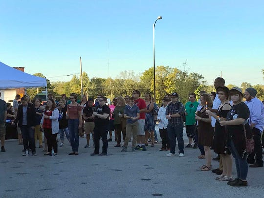 About 100 people gathered outside the GLO Center in