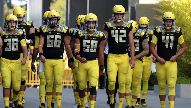Oregon Ducks long snapper Tanner Carew (58) walks out from the locker room with teammates before a game against the Eastern Washington Eagles at Autzen Stadium.