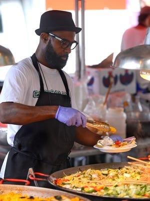 Stefan McGlashan serves up some seafood Sunday during the Pensacola Seafood Festival at Seville Square.