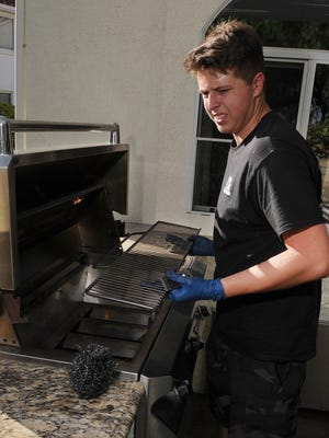 Robert Tomasi, 20, from BBQ Butlers, cleans a customer's barbecue grill in Newbury Park. The company, started by Tomasi and 17-year-old Matthew Glienke, is donating its profits to a veteran's nonprofit.