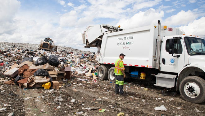 A City of Staunton garbage collector stands by as a truck unloads refuse at the Augusta Regional Landfill on Monday, April 20, 2015.