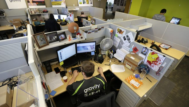 Austin Roos, a support team supervisor, works at lower left, Wednesday, April 15, 2015 at Gravity Payments, a credit card payment processor based in Seattle.