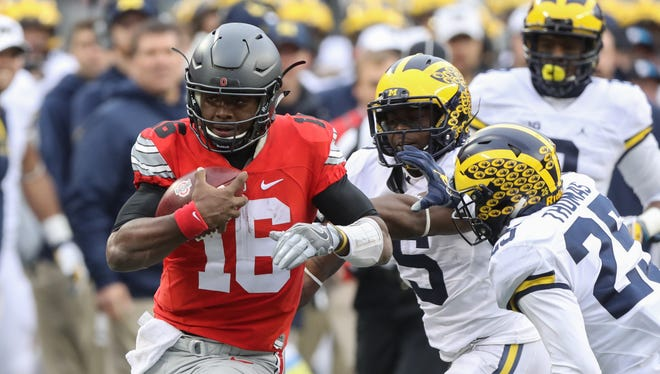 Michigan's Jabrill Peppers (5) and Dymonte Thomas pursue Ohio State's J.T. Barrett, who ran for a first down during the second half Saturday, Nov. 26, 2016 at Ohio Stadium.