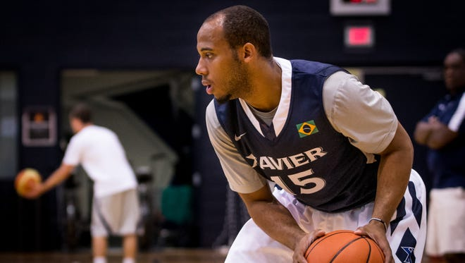 Sophomore guard Myles Davis gets ready to pass the ball during Xavier's basketball practice Monday.