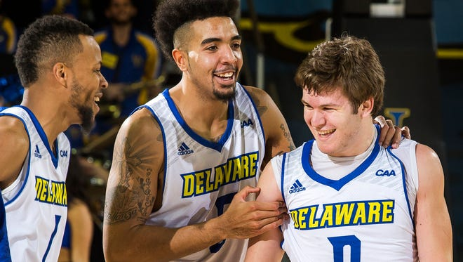 Delaware's Eric Carter (center) and Chivarsky Corbett (left) smile as they walk off the court with teammate Ryan Daly (right) following the University of Delaware's 69-62 win over Northeastern University at the Bob Carpenter Center in Newark on Thursday night.