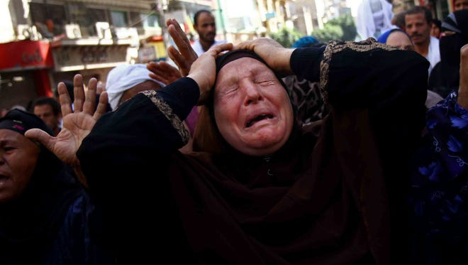 An Egyptian woman mourns after a judge in Egypt sentenced to death 683 alleged supporters of the country's ousted Islamist president in the southern city of Minya, Monday.