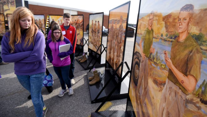 Students visit the Eyes of Freedom exhibit honoring the fallen soldiers of Lima Company on Tuesday afternoon outside Lexington High School. The soldier depicted to the far right is Marine Lance Cpl. Christopher P. Lyons of Shelby, Ohio, and a former employee at the Mansfield News Journal.