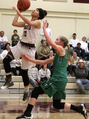 Tularosa's Cassie Vickery, left, attempts a layup Saturday evening.