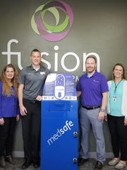 A new prescription drop box is installed at Fusion Pharmacy in Santa Clara as part of a community partnership that includes the following: Teresa Willie, Washington County Prevention Coalition Coordinator; Travis Snow and Travis Jackman, Fusion Pharmacists; and Amber Rich, Dixie Regional Medical Center Community Health Coordinator.
