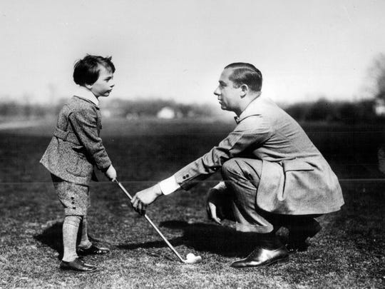 Golfer Walter Hagen instructs a very young friend.