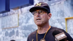 Michigan coach Jim Harbaugh speaks with the media during