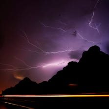 Lighning strikes over a butte while cars streak by on McDowell Rd. in Phoenix during a monsoon storm August 26, 2013.
