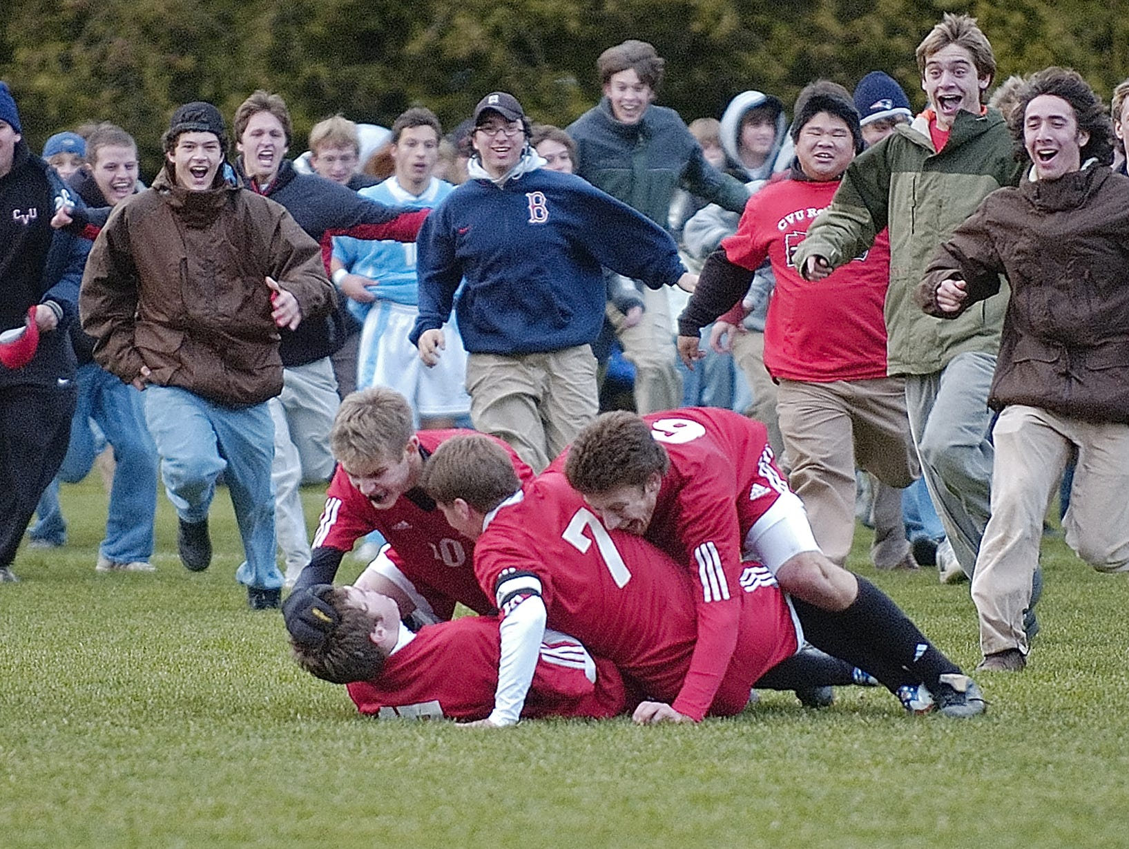 CVU's Tyler Macnee (bottom left) is mobbed by teammates Micah Rose, Ethan Morrow and Ian Dudley after Macnee scored the winning goal in the 2006 Division I boys soccer final against South Burlington.