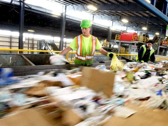 Penn Waste recycling center sorter Robert Pullo Jr., center, pulls items from a conveyor at the Manchester Township facility Friday, March 25, 2016. For the safety of sorters, Penn Waste is urging customers to contain medical waste items like needles and dispose of them in their regular trash. Bill Kalina photo