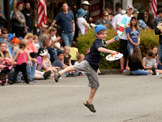 A youngster with a sword, shield and viking helmet leaps into the middle of the road prior to the start of the Viking Fest Parade in downtown Poulsbo, Washington on Saturday, May 19, 2018.